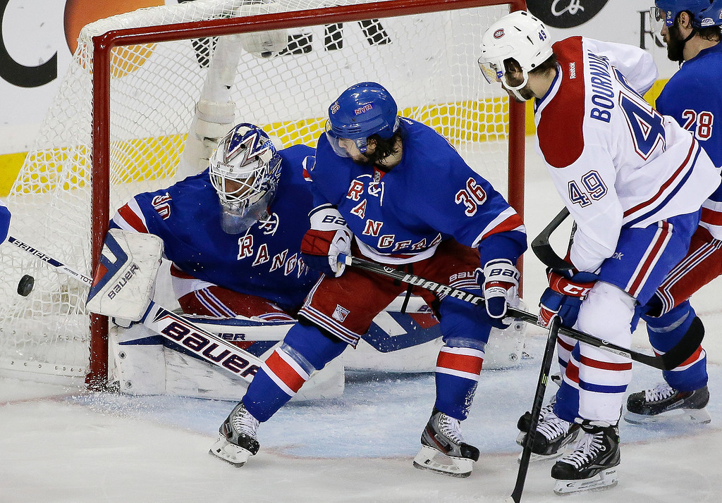 . New York Rangers goalie Henrik Lundqvist (30) deflects a shot on goal by the Montreal Canadiens as right wing Mats Zuccarello (36) helps defend and Montreal Canadiens left wing Michael Bournival (49) looks for the rebound during the first period in Game 6 of the NHL hockey Stanley Cup playoffs Eastern Conference finals, Thursday, May 29, 2014, in New York. (AP Photo/Frank Franklin II)