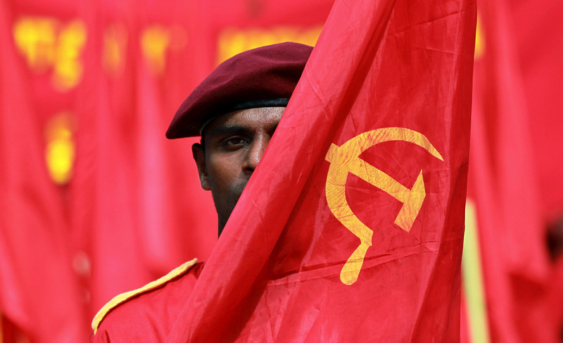 . A member of Sri Lanka\'s Marxist Party Peoples Liberation Front carries a flag symbolizing the working class during a parade held to mark the International Labor Day or May Day in Colombo, Sri Lanka, Thursday, May 1, 2014. (AP Photo/Eranga Jayawardena)