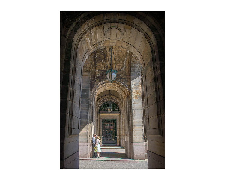 Wedding Photography of Blair & Adam,  Glasgow, Scotland, Photograph is of the Bride & Groom standing in the sun in a series of arches