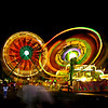 Fair rides viewed at night.  Families and friends enjoy the rides and excitement.