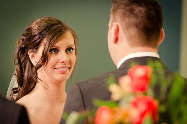 Elegant bride gazes lovingly at groom during wedding at Trinity Lutheran Church in Rockford, IL