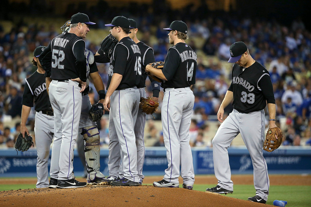 . Coach Jim Wright #52 of the Colorado Rockies talks to pitcher Tyler Matzek #46 at the mound in the third inning during the MLB game against the Los Angeles Dodgers at Dodger Stadium on June 16, 2014 in Los Angeles, California.  (Photo by Victor Decolongon/Getty Images)