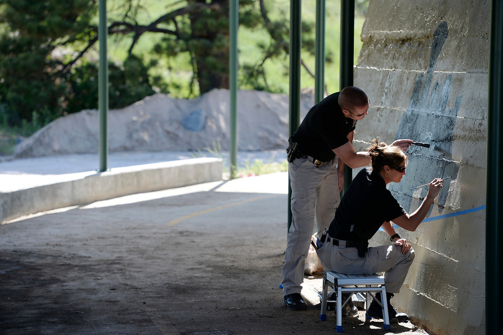 . Castle Rock police officer Renee Tremaine and Special Operations Seth Morrissey paint at Hangmans Gulch underpass June 9, 2014 along the Plum Creek trail. They plan on painting 12 underpasses throughout the town. (Photo by John Leyba/The Denver Post)