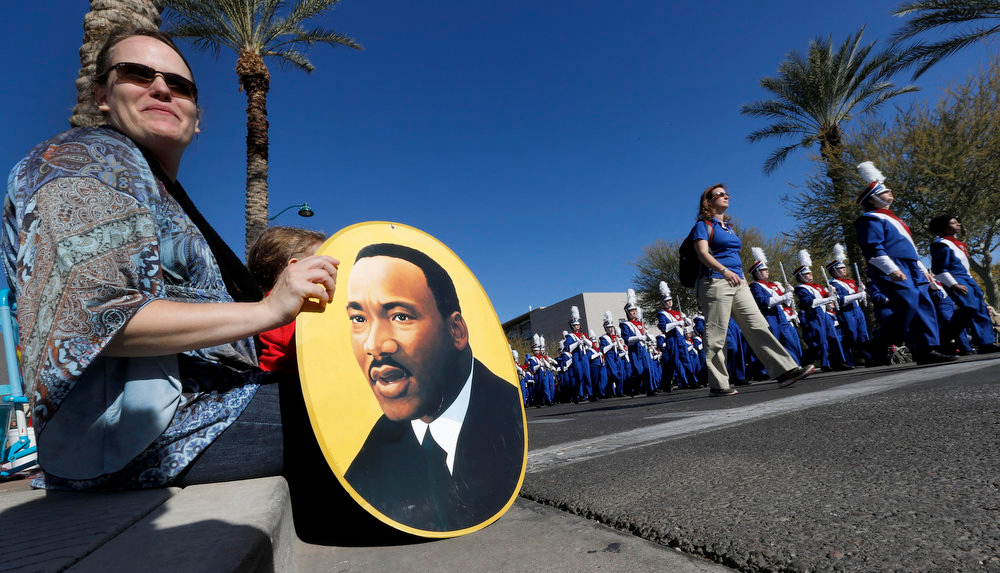 . Michelle Dahlke and her son, Ashton Dahlke, 4, watch a band during the MLK Day parade, Monday, Jan. 21, 2013 in Mesa, Ariz. The nation honored civil rights leader Martin Luther King Jr. on Monday. (AP Photo/Matt York)