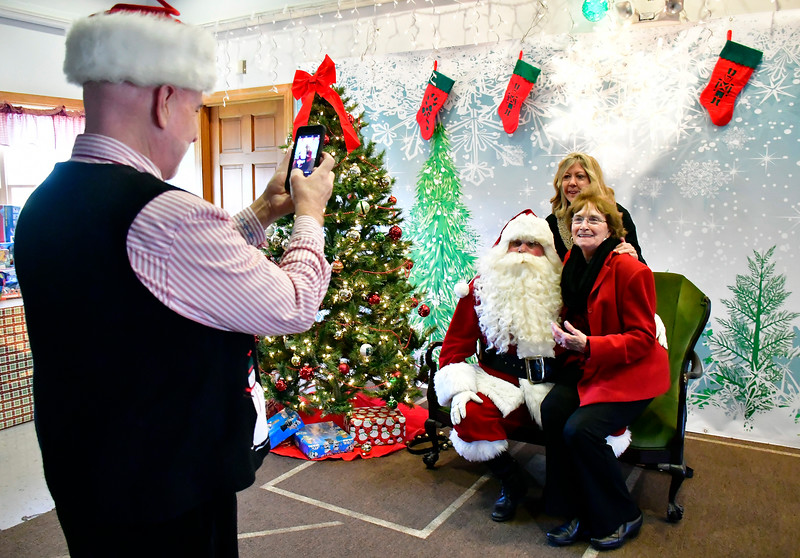 12/01/2018 Mike Orazzi | Staff Santa's helper Kevin Prior photographs Doreen Jayne Stickney and her mom Joanne Jayne during the 25th Annual Breakfast with Santa at the Giamatti Little League Center Saturday in Bristol.