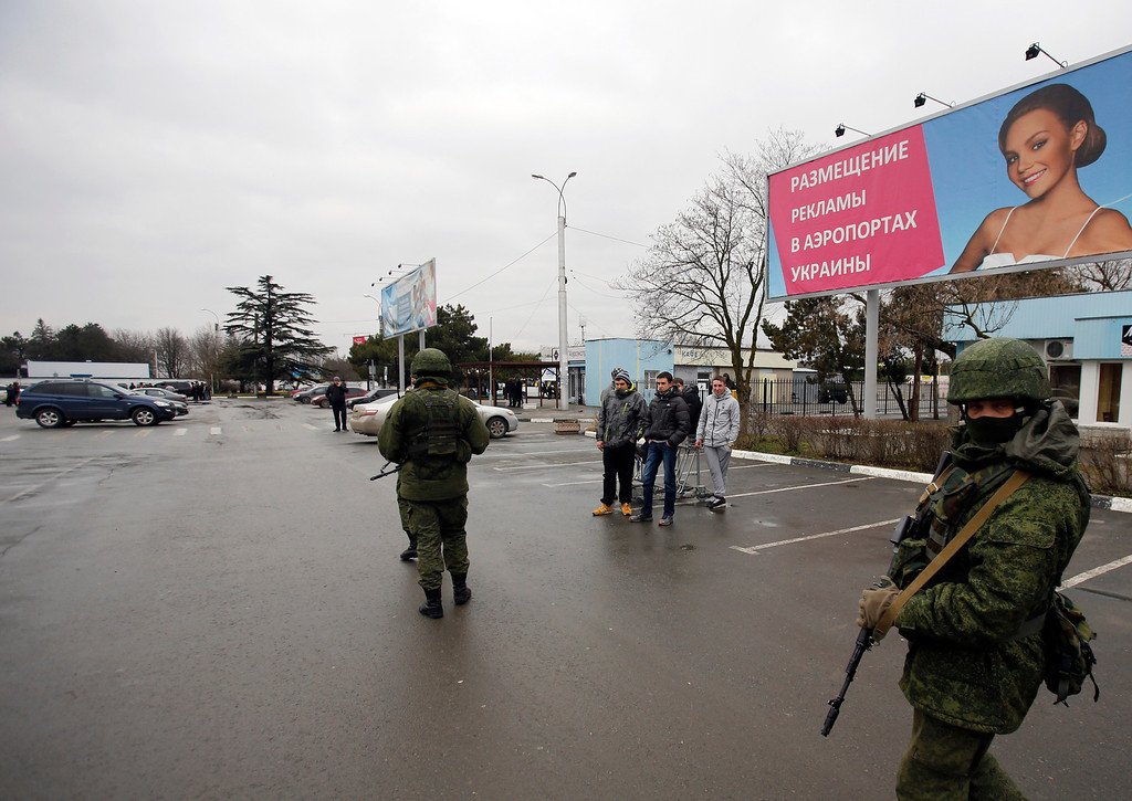 . Unidentified armed men patrol in front of the airport in Simferopol, Ukraine, Friday, Feb. 28, 2014.   (AP Photo/Darko Vojinovic)