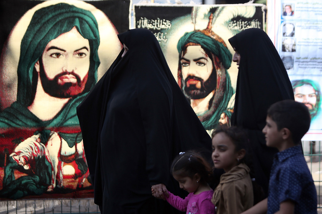 . Iraqi Shiite women walk past posters with the image of Imam Hussein during a parade in preparation for the peak of the mourning period of Ashura in Baghdad\'s northern district of Kadhimiya on November 1, 2014.  AHMAD AL-RUBAYE/AFP/Getty Images