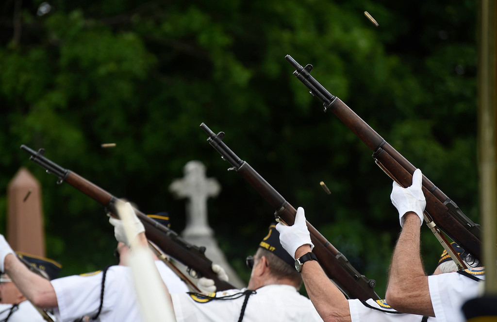 . Kayla Rice/Reformer Members of the Brattleboro VFW Honor Guard shoot their rifles into the air during the Memorial Day service at St. Michael\'s cemetery in Brattleboro on Monday morning.