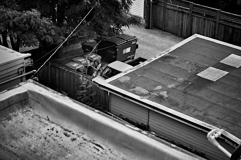 A man living in the alley swings a cord at a man standing next to a fence.  He was ranting and seemed unstable. The other man was unharmed.Police were called, but I don't believe he was arrested, despite his aggressive behavior towards anyone who came close.  Captured from the 4th floor of my townhome.