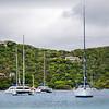 Several luxury catamarans and sailboats anchored along shore of an island.