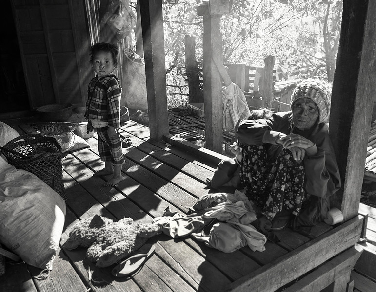 A grandmother from the Muun tribe sitting with her grandson outside their wooden house. Most tribal families in this part of Myanmar live in large numbers close together in wooden houses made by themselves.  Chin State, Myanmar, 2017