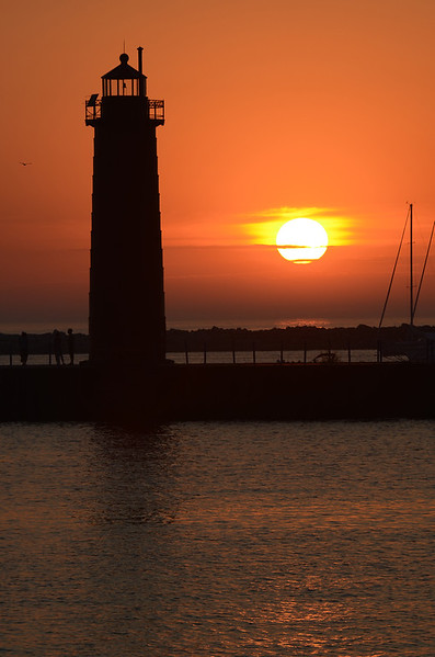 Sun setting behind the light house near the entrance to the channel to Lake Muskegon as seen from the State Park nearby.