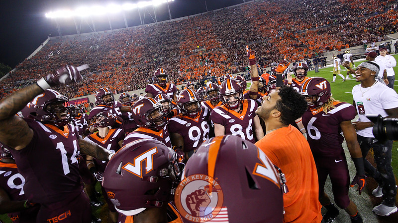 Injured QB Josh Jackson (orange) pumps up the team at the end of their warmups. (Mark Umansky/TheKeyPlay.com)
