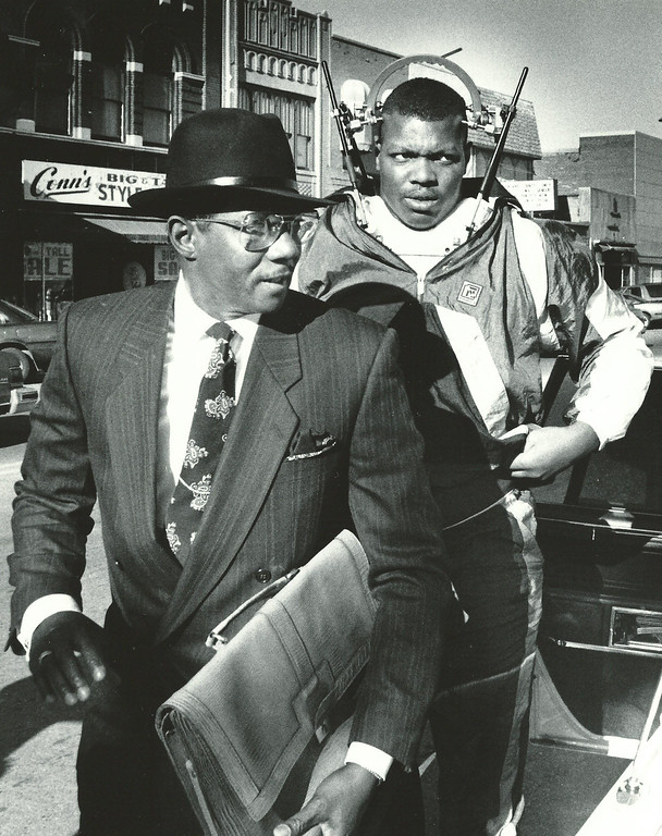 . Former Detroit Lions player Reggie Rogers (wearing halo neck brace) arrives at 50th District Court in Pontiac in Nov. 1988 via limousine with attorney Elbert Hatchett. The Oakland Press/file photo