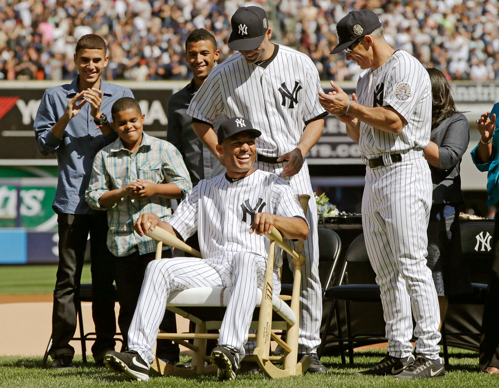 . New York Yankees manager Joe Girardi, far right, and Derek Jeter, center, above Rivera, watch as relief pitcher Mariano Rivera tries out a rocking chair they presented to him during a pregame ceremony at Yankee Stadium before a baseball game agains the San Francisco Giants, Sunday, Sept. 22, 2013, in New York. Rivera\'s three sons, Jafet, Jaziel and Mariano Jr. watch from left. AP Photo/Kathy Willens)