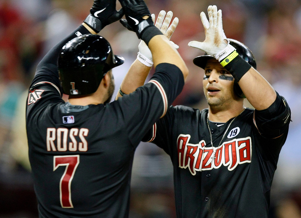 . Arizona Diamondbacks Martin Prado (14), right, celebrates with Cody Ross (7) after hitting a two-run home run in the seventh inning during a baseball game against the Colorado Rockies on Saturday, July 6, 2013, in Phoenix. (AP Photo/Rick Scuteri)