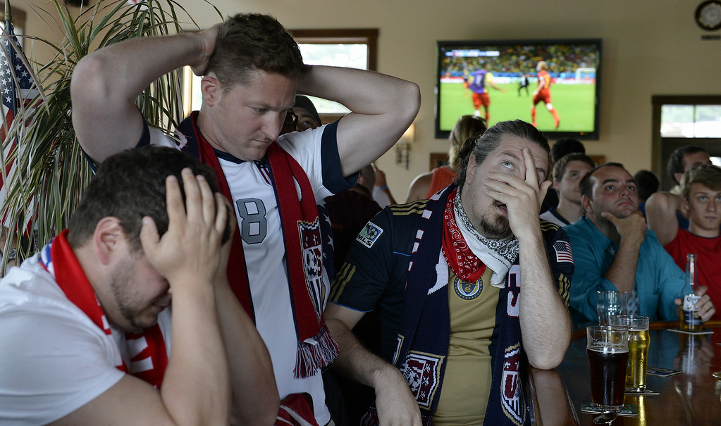 . United States soccer fans John Goodison, Paul Vranesic and Chris Bomgardmer react after a goal scored by Belgium in a World Cup match where the United States fell to Belgium 2-1 on Tuesday, July 1, 2014, Cornwall, Pa. (AP Photo/Lebanon Daily News, Jeremy Long)