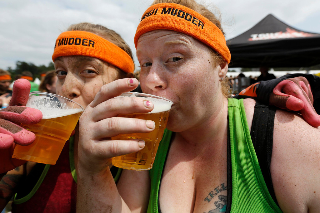 ". Heather Cozad (R) of the U.S. drinks beer with a friend after finishing the ""Tough Mudder\"" endurance event series in the Fursten Forest, a former British Army training ground near the north-western German city of Osnabrueck July 13, 2013. The hardcore but un-timed event over 16 km (10 miles) was designed by British Special Forces to test mental as well as physical strength. Some 4,000 competitors had to overcome obstacles of common human fears, such as fire, water, electricity and heights. REUTERS/Wolfgang Rattay"