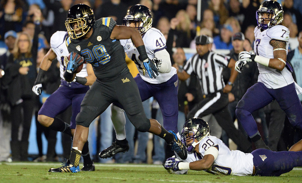 . UCLA Bruins running back Malcolm Jones (28) runs for a first down against Washington Huskies during the first half of their college football game in the Rose Bowl in Pasadena, Calif., on Friday, Nov. 15, 2013.  UCLA won 41-31.   (Keith Birmingham Pasadena Star-News)