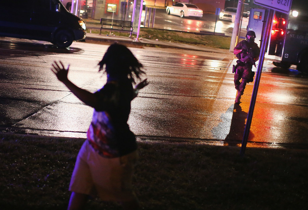 . FERGUSON, MO - AUGUST 15:  A Police officer confronts a demonstrators during a protest over the shooting death of Michael Williams on August 15, 2014 in Ferguson, Missouri. Police shot pepper spray,  smoke, gas and flash grenades at protestors before retreating. Several businesses were looted as the county police sat nearby with armored personnel carriers (APC). Violent outbreaks have taken place in Ferguson since the shooting death of Brown by a Ferguson police officer on August 9.  (Photo by Scott Olson/Getty Images)