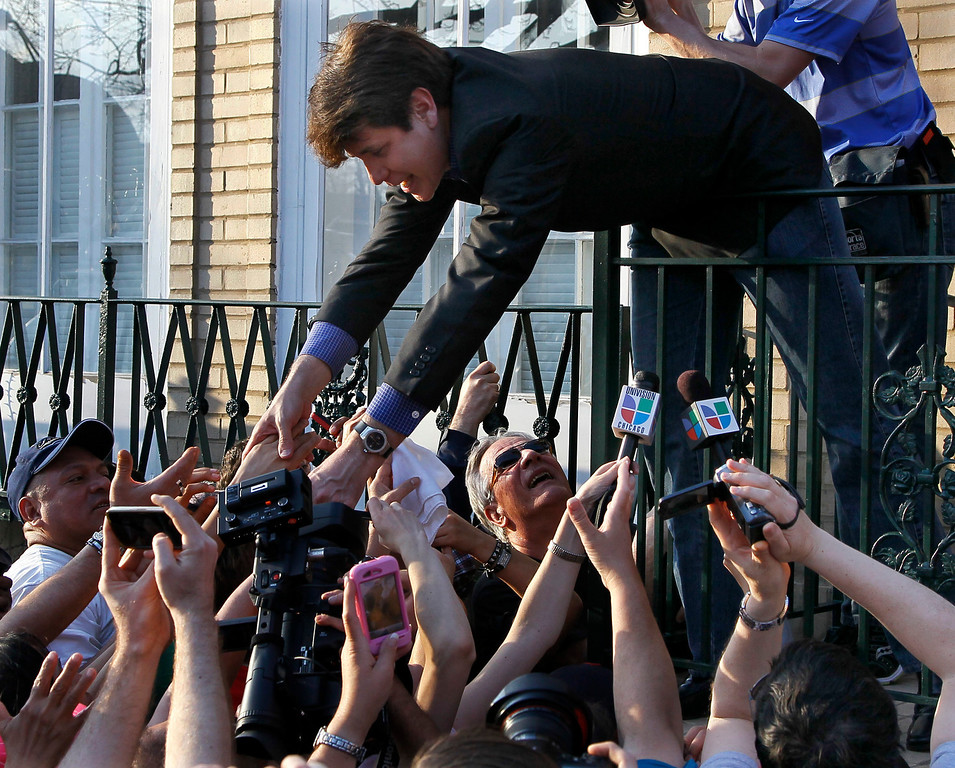 . In this March 14, 2012 file photo, former Illinois Gov. Rod Blagojevich reaches over a railing to shake supporters\' hands at his home in Chicago. The 55-year-old Democrat was due to report to a prison in Colorado to begin serving a 14-year sentence, making him the second Illinois governor in a row to go to prison for corruption. (AP Photo/Charles Rex Arbogast, File)