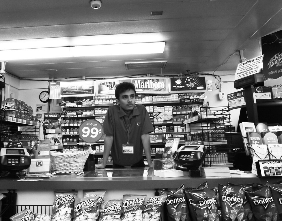 . I work at a gas station. This is me standing at the counter during a graveyard shift when there was nobody inside. This picture is black and white because nobody would want to work a graveyard shift at a gas station and I thought that making it black and white would tell the story. If this picture is colorful it would probably mean something else but since its black and white it�s a sad image. It�s me at 12am, alone, doing nothing, kind of scary, but nothing happened that day. I�m in college now and when I think about me working after ten years, you know, when I look at myself, I don�t see myself as something very specific but I have a dream inside me and everyday when I wake up I think about that dream. I feel like I need to go somewhere out of this country and there is someone who I can help there. I will be whatever I have to be to help that person, or those children or someone else. It could be the doctor in me, it could be a teacher in me, it could be a photographer in me, it could be a soccer player in me but I want to go help them. I don�t know maybe I will be shocked when I have to do something I don�t like but let it be. My ultimate goal is to get there and help them and be happy. I think I will have a smile when I go there and I get to help them. I remember when I was in the refugee camp I would see United Nations workers there who didn�t speak Nepali. Even in the refugee camp I thought I want to be like them. I want to help others. I always felt I was more privileged then others. I had a poster on my wall from the World Refugee Day somewhere in Africa. It was of long line of people on a bridge getting kicked out of their country, I always thought, I have school to go to in the refugee camp. I have clothes. I have a hut of bamboo. I had something over my head that was protecting me from the rain, so I always thought I was more privileged. I thought I was not asking for something because I was helpless. I thought there were other people who needed help ev