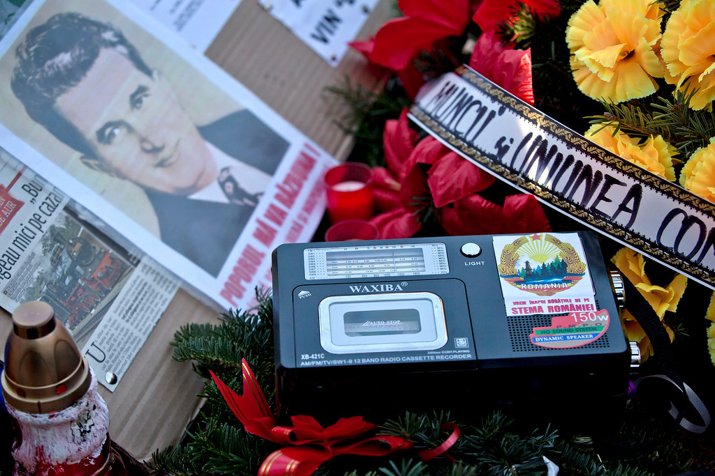 . A cassette player airs a recording of the last speech, on Dec. 21, 2014,  by Romanian communist dictator Nicolae Ceausescu as communism nostalgics gather around his grave in Bucharest, Romania,  Thursday, Dec. 25, 2014, 25 years after he and his wife Elena were executed by firing squad on Christmas day 1989. Romanians, especially those of a more senior age, have mixed feelings about the former dictator and his rule, 25 years after his execution, with many remembering predominantly the positive aspects, like the social security, of the communist times and not focusing on the extreme economic hardships and lack of basic human rights of that period, like freedom of movement or speech.  (AP Photo/Vadim Ghirda)