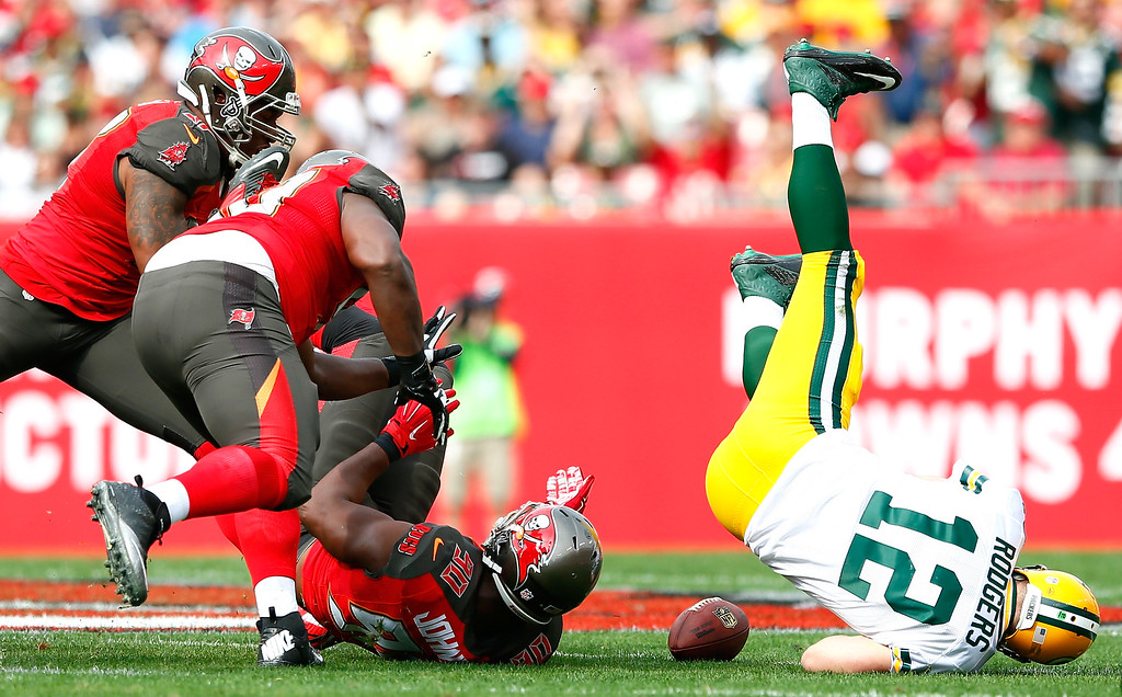 . TAMPA, FL - DECEMBER 21:  Michael Johnson #90 of the Tampa Bay Buccaneers forces a fumble by Aaron Rodgers #12 of the Green Bay Packers at Raymond James Stadium on December 21, 2014 in Tampa, Florida.  (Photo by Kevin C. Cox/Getty Images)
