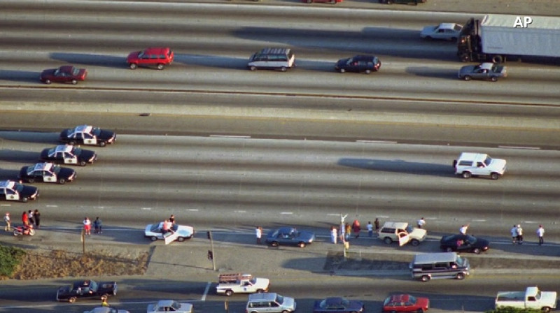 . A white Ford Bronco, driven by Al Cowlings and carrying O.J. Simpson, is trailed by police cars on June 17, 1994, in Los Angeles.  Cowlings and Simpson led authorities on a chase after Simpson was charged with two counts of murder in the deaths of his ex-wife and her friend.  (AP)