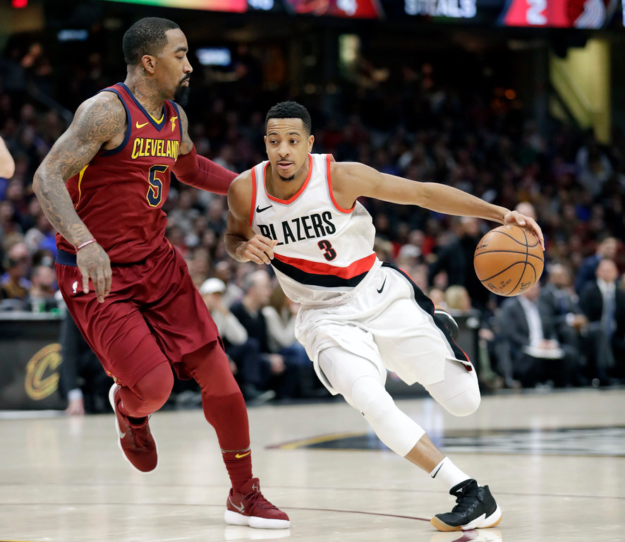 . Portland Trail Blazers\' CJ McCollum (3) drivers past Cleveland Cavaliers\' JR Smith (5) in the first half of an NBA basketball game, Tuesday, Jan. 2, 2018, in Cleveland. (AP Photo/Tony Dejak)