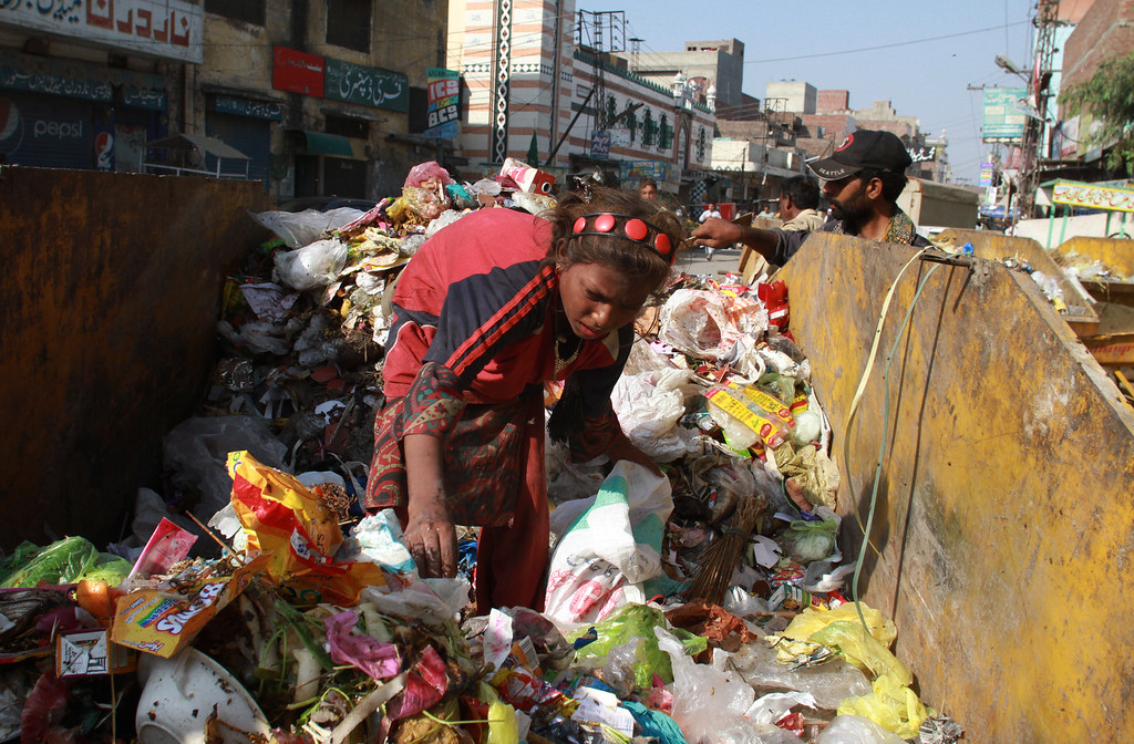 . A poor Pakistani girl collects recyclable items to sell and earn her living, in Lahore, Pakistan, Friday, Oct. 17, 2014. (AP Photo/K.M. Chaudary)