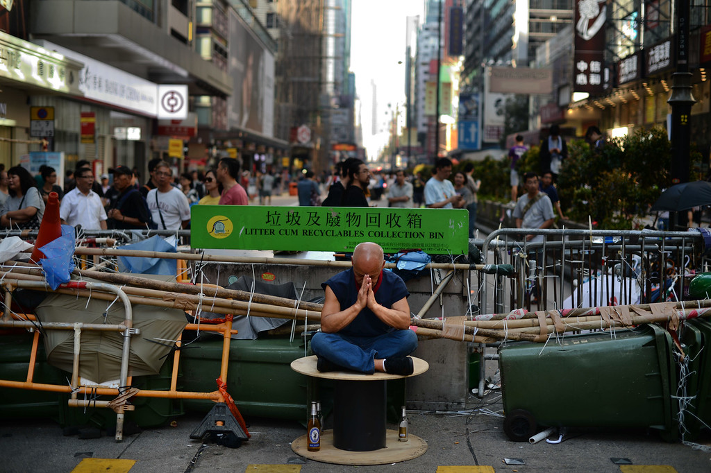 . A man rests in front of a barricade in an area taken by pro-democracy demonstrators in Mong Kok district in Hong Kong on October 18, 2014. Hong Kong\'s embattled government said it will open talks with student demonstrators Tuesday, after three nights of violent clashes between police and protesters who have paralysed parts of the city with mass pro-democracy rallies. AFP PHOTO/Pedro UgartePEDRO UGARTE/AFP/Getty Images