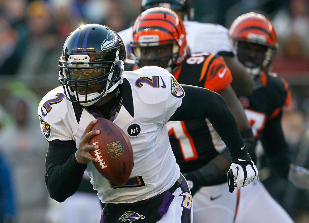 . Baltimore Ravens quarterback Tyrod Taylor (2) fights to break free from Cincinnati Bengals\' Robert Geathers (91) during the first half of play in their NFL football game at Paul Brown Stadium in Cincinnati, Ohio, December 30, 2012.      REUTERS/John Sommers II