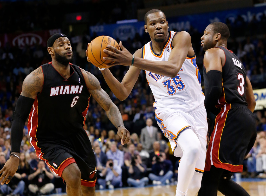 . Oklahoma City Thunder forward Kevin Durant (35) drives between Miami Heat forward LeBron James (6) and guard Dwyane Wade (3) during the fourth quarter of an NBA basketball game in Oklahoma City, Thursday, Feb. 20, 2014. Miami won 103-81. (AP Photo/Sue Ogrocki)
