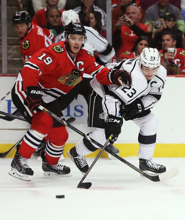 . Jonathan Toews #19 of the Chicago Blackhawks and Dustin Brown #23 of the Los Angeles Kings vie for the puck in the second period of Game One of the Western Conference Final during the 2014 Stanley Cup Playoffs at United Center on May 18, 2014 in Chicago, Illinois.  (Photo by Jonathan Daniel/Getty Images)