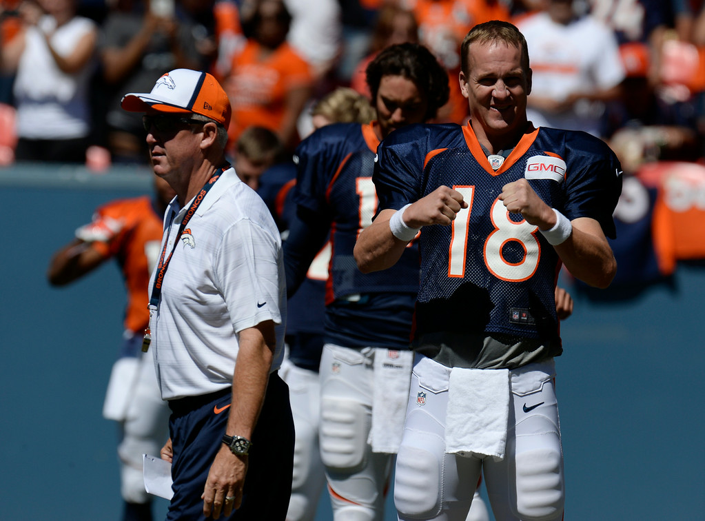 . Denver Broncos head coach, John Fox, walks past QB, Peyton Manning during stretching before practice and scrimmage at Sports Authority Field at Mile High Saturday afternoon, August 02, 2014. (Photo By Andy Cross / The Denver Post)