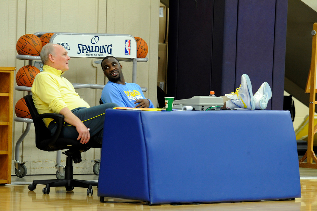 . Head coach George Karl of the Denver Nuggets chats with Ty Lawson at the table during practice April 22, 2013 at Pepsi Center. The Denver Nuggets prepare for game two of the first round of the NBA playoffs against the Golden State Warriors. (Photo By John Leyba/The Denver Post)