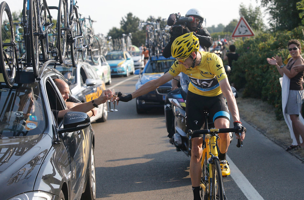. Christopher Froome of Britain, wearing the overall leader\'s yellow jersey, toasts with a glass of champagne at his team car during the 21st and last stage of the 100th edition of the Tour de France cycling race over 133.5 kilometers (83.4 miles) with start in Versailles and finish in Paris, France, Sunday July 21 2013.  (AP Photo/Laurent Cipriani)