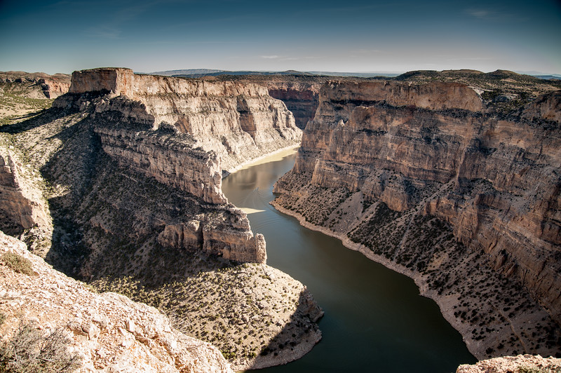 The Bighorn River flows through the striated beige walls of Bighorn Canyon.