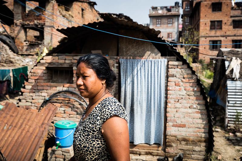 A woman in front of the temporary shelter where she still lives, two years after the earthquakes in Nepal. Pokhara, Nepal. March 2017 ----------- Une femme devant l'abri temporaire où elle vit encore, deux ans après les tremblements de terre au Népal. Pokhara, Népal. Mars 2017