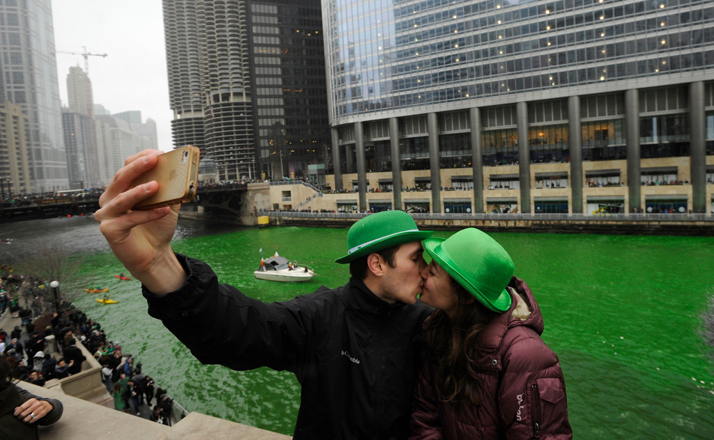 . John Shepard and Gena Damento of Rochester Minn., take a photo of themselves kissing after the Chicago River was dyed green ahead of the St. Patrick\'s Day parade in Chicago, Saturday, March, 16, 2013.  With the holiday itself falling on a Sunday, many celebrations were scheduled instead for Saturday because of religious observances. (AP Photo/Paul Beaty)