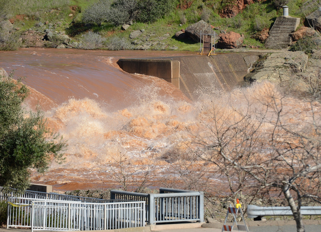 . Water flows over the Fish Barrier Dam in as a muddy Feather River flows Saturday, Feb. 11, 2017, in Oroville, California. (Dan Reidel -- Enterprise-Record)