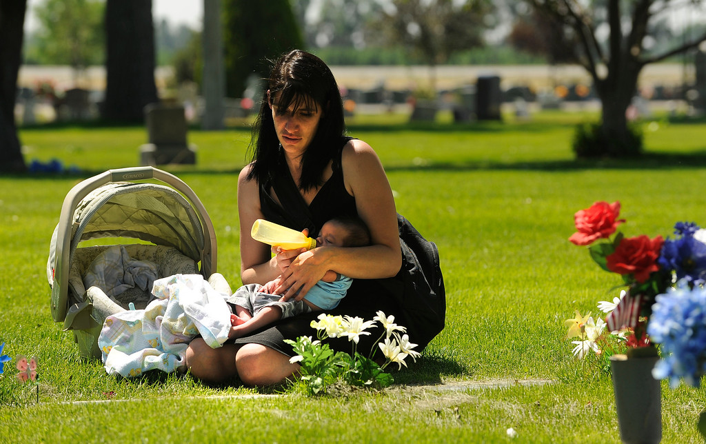 . Krista Adams, with her new five-week-old baby son, Michael Adams, visits the grave of her son, Julian Adams Lacas, Friday, June 06, 2012, at Elmwood Cemetery in Brighton. Her son was killed  by his father who is currently serving a 48 year prison sentence. This was the first time she has brought her new son to grave site. Krista Adams brought her sister Melissa Adams with her for support. RJ Sangosti, The Denver Post