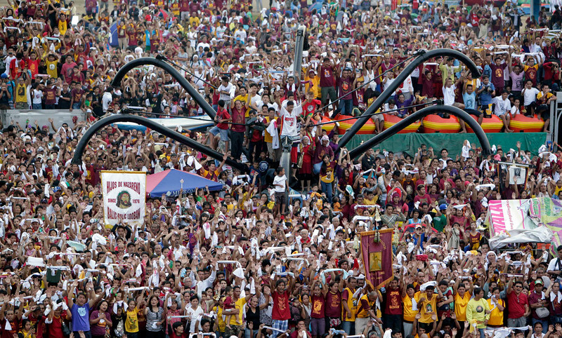 . Devotees pray in an amusement park as they look at the statue of the Black Nazarene (not pictured) during a procession in Manila January 9, 2013. The Black Nazarene, a life-size wooden statue of Jesus Christ carved in Mexico and brought to the Philippines in the 17th century, is believed to have healing powers in the predominantly Roman Catholic country. It is paraded through the narrow streets of Manila\'s old city from dawn to midnight. Police said about 500,000 people joined the procession on Wednesday. REUTERS/Erik De Castro