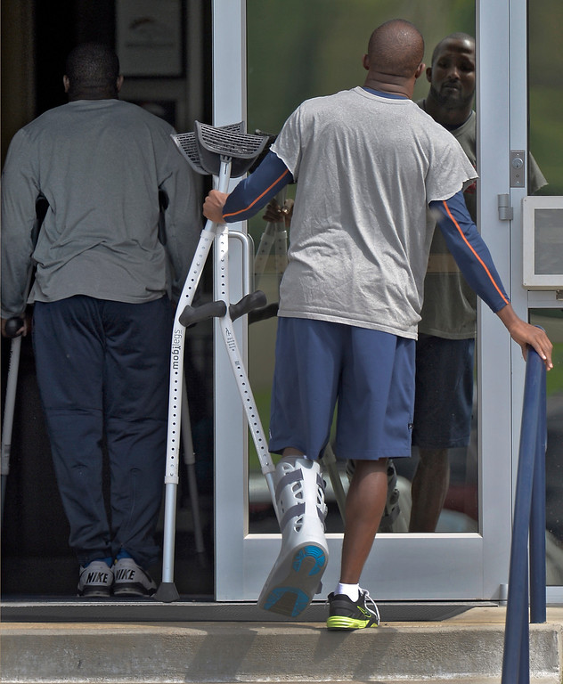 . Denver Broncos cornerback Champ Bailey walks to his rehab session at the Broncos conditioning center just behind C.J. Anderson, in crutches, during practice August 23, 2013 at Dove Valley. Bailey was wearing a walking boot cast and crutches. (Photo by John Leyba/The Denver Post)
