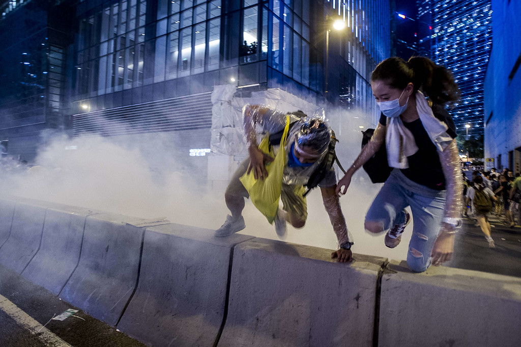 . Pro-democracy run away during a demonstration in Hong Kong on September 28, 2014. Police fired tear gas as tens of thousands of pro-democracy demonstrators brought parts of central Hong Kong to a standstill on September 28, in a dramatic escalation of protests that have gripped the semi-autonomous Chinese city for days. It marked a dramatic escalation of protests in the city, which rarely sees such violence, after a tense week of largely contained student-led demonstrations exploded into mass angry street protests.  AFP PHOTO / XAUME OLLEROSXAUME OLLEROS/AFP/Getty Images