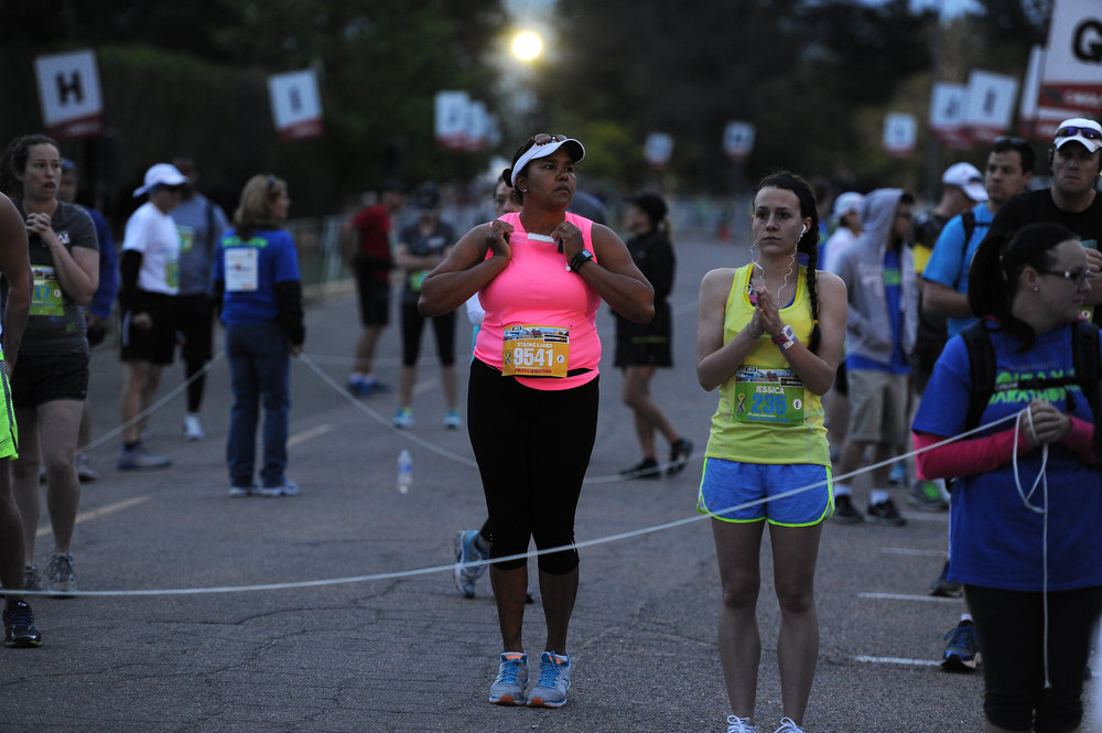 . Marathon runners Babette Hudson-Tsao, in pink, and Jessica Merriman, in yellow, try to keep warm in the pre-dawn hours before the start of the Colfax marathon in City Park in Denver, CO on May 19th, 2013.  (Photo by Helen H. Richardson/The Denver Post)