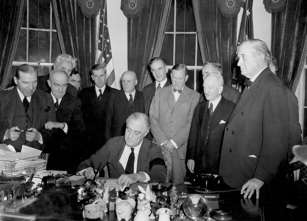 . U.S. President Franklin D. Roosevelt signs the declaration of war following the Japanese bombing of Pearl Harbor, Dec. 7, at the White House in Washington, D.C., Dec. 8, 1941 at 3:08 p.m. EST.  Watching from left to right are, Rep. Sol Bloom, D-N.Y.; Rep. Luther Johnson, D-Texas; Rep. Charles A. Eaton, R-N.J.; Rep. Joseph Martin, R-Mass.; Vice President Henry A. Wallace; House Speaker Sam Rayburn, D-Texas; Rep. John McCormack, D-Mass.; Sen. Charles L. McNary, R-Ore.; Sen. Alben W. Barkley, D-Ky.; Sen. Carter Glass, D-Va.; and Sen. Tom Connally, D-Texas.  (AP Photo)