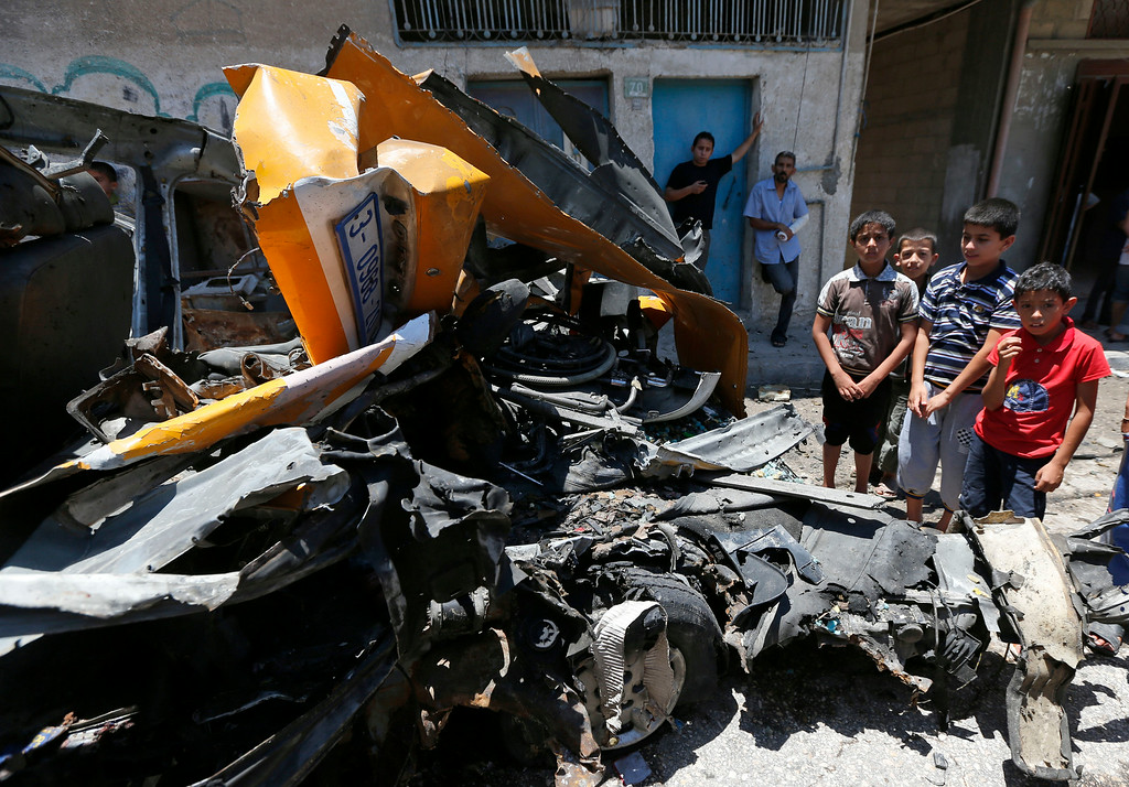 . Palestinians gather around a vehicle that was destroyed by a Israeli missile strike in Khan Younis, southern Gaza Strip on Wednesday, July 16, 2014. Hundreds of Palestinian families, their children crying, fled Wednesday, as Israel intensified airstrikes on Hamas targets, including homes of the movement\'s leaders, following failed Egyptian cease-fire efforts. Before the renewed bombardment, Israel had told tens of thousands of residents of border areas to evacuate their neighborhoods. (AP Photo/Lefteris Pitarakis)