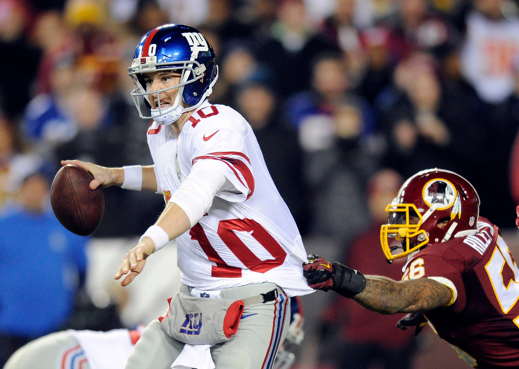 . New York Giants quarterback Eli Manning (10) looks to pass as Washington Redskins inside linebacker Perry Riley hangs onto his jersey during the second half of an NFL football game Sunday, Dec. 1, 2013, in Landover, Md. (AP Photo/Nick Wass)